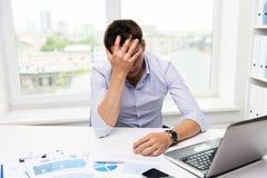 Homem de negócios com portátil e papéis no escritório Imagens de Stock Royalty Free