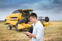 Homem de negócios com portátil e telefone celular no campo Fotografia de Stock Royalty Free