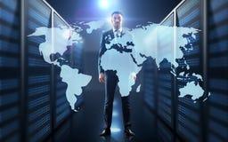 Homem de negócios com projeção de mapa do mundo no corredor Fotografia de Stock Royalty Free