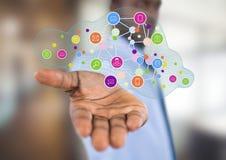 homem de negócios com propagação da mão com de ícones da aplicação sobre ESCRITÓRIO BORRADO Foto de Stock Royalty Free
