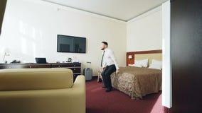 Homem de negócios com sala de hotel entrando da bagagem e salto no sorriso relaxado felizmente então de encontro da cama Curso, n vídeos de arquivo