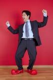 Homem de negócios com sapatas do palhaço Fotos de Stock