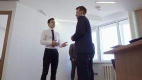 Homem de negócios com seus suportes do colega no escritório e para discutir o trabalho vídeos de arquivo