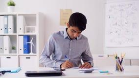 Homem de negócios com smartphone e papéis no escritório filme
