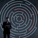 Homem de negócios com a tabuleta do computador que está sobre o backgro do labirinto Imagens de Stock Royalty Free