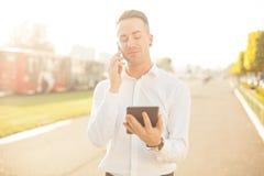 Homem de negócios com a tabuleta do telefone celular nas mãos Imagens de Stock