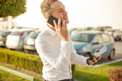 Homem de negócios com a tabuleta do telefone celular nas mãos Imagens de Stock Royalty Free