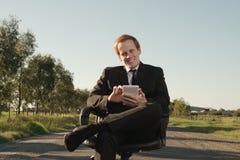 Homem de negócios com a tabuleta exterior Imagem de Stock Royalty Free