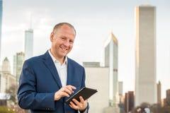 Homem de negócios com a tabuleta na frente dos prédios de escritórios Foto de Stock