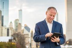 Homem de negócios com a tabuleta na frente dos prédios de escritórios Fotografia de Stock Royalty Free