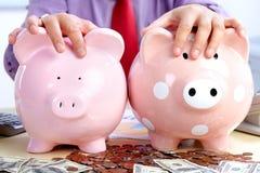 Homem de negócios com um banco do porco Imagens de Stock