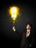 Homem de negócios com um bulbo eco-amigável Imagem de Stock