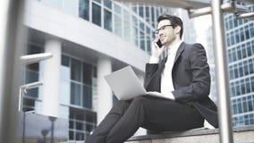 Homem de negócios com um portátil que tem uma chamada no ao ar livre Fotos de Stock
