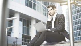Homem de negócios com um portátil que tem uma chamada no ao ar livre Fotografia de Stock Royalty Free