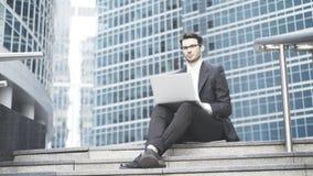 Homem de negócios com um portátil que trabalha no ao ar livre Fotografia de Stock Royalty Free