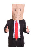 Homem de negócios com um saco de papel com sorriso na cabeça que mostra o sinal aprovado Fotografia de Stock