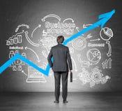 Homem de negócios com uma mala de viagem que olha um gráfico azul crescente e um esboço da estratégia empresarial foto de stock