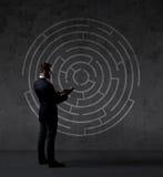 Homem de negócios com uma tabuleta que está em um labirinto Fotos de Stock Royalty Free