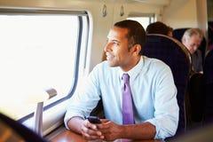 Homem de negócios Commuting To Work no trem usando o telefone celular Fotografia de Stock Royalty Free