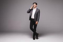 Homem de negócios completo da altura que fala no telefone celular isolado em um fundo cinzento Fotografia de Stock Royalty Free