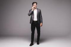 Homem de negócios completo da altura que fala no telefone celular isolado em um fundo cinzento Imagem de Stock