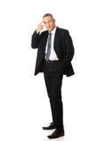 Homem de negócios completo do comprimento que gesticula o sinal do idiota Imagem de Stock Royalty Free