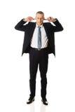 Homem de negócios completo do comprimento que obstrui suas orelhas Fotos de Stock