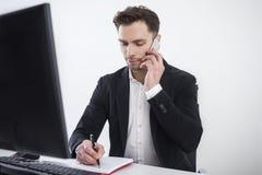 Homem de negócios concentrado no telefone Imagens de Stock Royalty Free