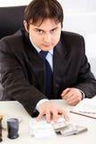 Homem de negócios concentrado que dá blocos do dinheiro Imagens de Stock Royalty Free