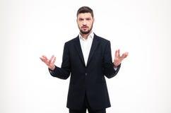 Homem de negócios confundido considerável com a barba que guarda o copyspace em ambas as mãos Imagens de Stock Royalty Free
