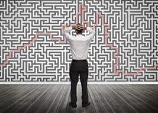 Homem de negócios confuso que olha um labirinto Fotografia de Stock
