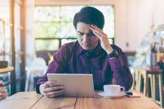 Homem de negócios considerável asiático novo concentrado ao ler o seu Fotos de Stock