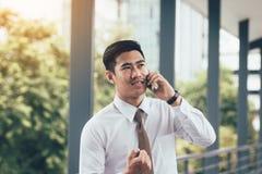 Homem de negócios considerável asiático novo que fala no telefone e na felicidade fotografia de stock