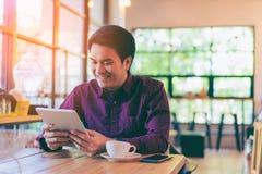 Homem de negócios considerável asiático novo que sorri ao ler sua tabela Imagem de Stock