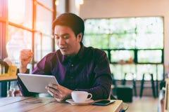 Homem de negócios considerável asiático novo que sorri ao ler sua tabela Fotos de Stock
