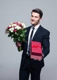 Homem de negócios considerável com flores e caixa de presente Fotografia de Stock