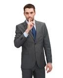 Homem de negócios considerável com o dedo em seus bordos Foto de Stock Royalty Free