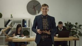 Homem de negócios considerável com a tabuleta digital no escritório filme
