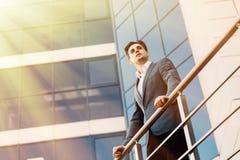 Homem de negócios considerável no balcão do prédio de escritórios que olha para a frente para o objetivo novo fotografia de stock royalty free