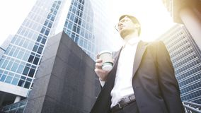 Homem de negócios considerável nos vidros que bebe o café em uma baixa Imagens de Stock Royalty Free