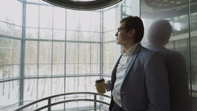 Homem de negócios considerável novo no café bebendo do terno que abaixa dentro do eleavator no centro de negócios moderno filme