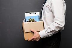 Homem de negócios considerável novo no escritório moderno claro com caixa da caixa Último dia no trabalho O trabalhador de escrit imagens de stock royalty free