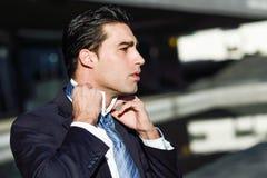 Homem de negócios considerável novo que ajusta um laço no fundo urbano Imagens de Stock