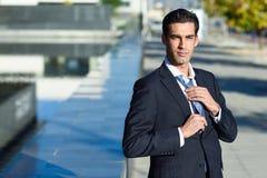 Homem de negócios considerável novo que ajusta um laço no fundo urbano Imagem de Stock