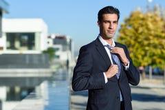 Homem de negócios considerável novo que ajusta um laço no fundo urbano Imagens de Stock Royalty Free