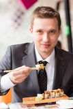 Homem de negócios considerável novo que come o sushi com varas Imagens de Stock