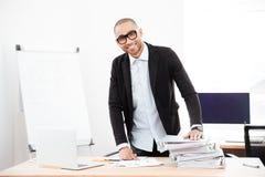 Homem de negócios considerável novo que está na mesa no escritório imagens de stock