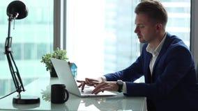 Homem de negócios considerável novo que trabalha no computador em seu escritório video estoque