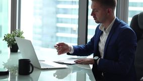 Homem de negócios considerável novo que trabalha no computador em seu escritório vídeos de arquivo