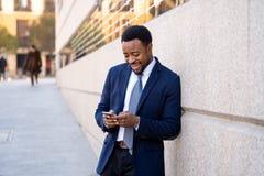 Homem de negócios considerável novo que usa o app do telefone celular que envia a mensagem fora do escritório na cidade urbana imagem de stock